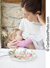 baby breastfeeding mother in restaurant
