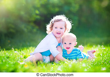 Baby brother and toddler sister in a garden