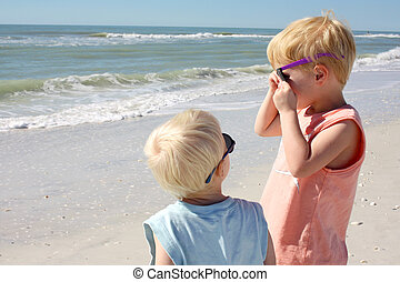 Baby Brother Looking at Older Child on Beach