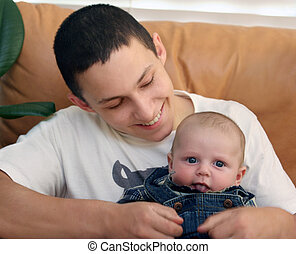 Baby brother - Happy teenage boy playing with a baby