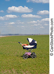 Baby buggy in spring standing alone on green grass field