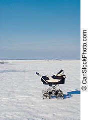 Baby buggy in winter standing alone in white snowy field