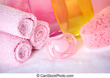 Baby care objects. Olive, shampoo in background towels, ...