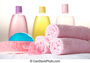 Baby care objects. Olive, shampoo, soap in background towels, sponge, soap and dummy