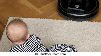 Baby carpet watching vacuum cleaner - Baby crawls on mat and...