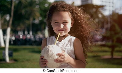 Baby caucasian, little girl with curly hair, in a white dress, drinking coconut.