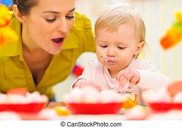 Baby celebrating first birthday with mom