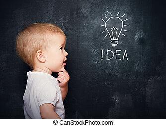 baby child at the blackboard with chalk drawn bulb symbol...