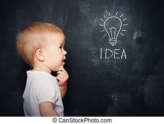 baby child at the blackboard with chalk drawn bulb symbol...