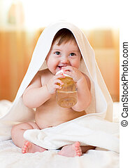Baby child girl drinks water from bottle wrapped towel at home