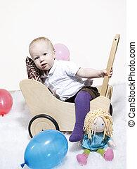 Baby climbing into dolls pram