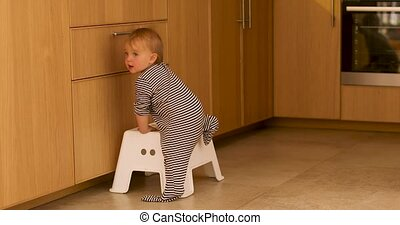 Baby climbing step stool in kitchen - Back view of baby in...