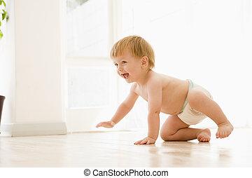 Baby crawling indoors smiling