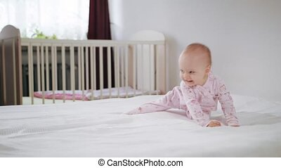 Baby Crawling on All Fours on the Bed - A baby crawling on...