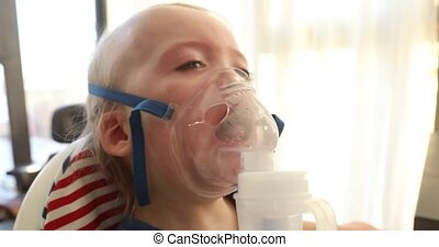 Baby crying and wear oxygen mask. Boy cries in the mask of...