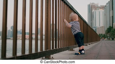 Baby cute dancing holding hands on the railing on the...