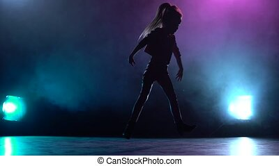 Baby dances jazz funk. Multicolor smoke background. Silhouette. Light from behind
