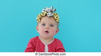 Baby decorated with a bow as a gift on a blue background