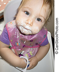 baby dirty face white yogurt in high-chair