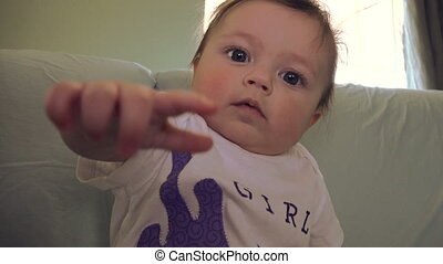 Baby Discovering She Has Control - A cute baby looking at...