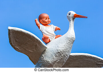Baby doll sitting on stork with blue sky