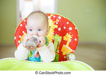 baby drinking from bottle sitting in high chair