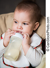 baby drinking milk from a bottle in the apartment