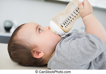 Baby drinking milk while lying on counter
