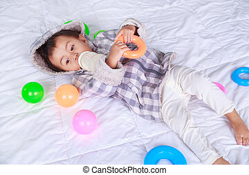 baby drinking milk with bottle on bed