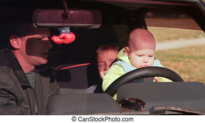 baby driver - father and two sons having fun in the car