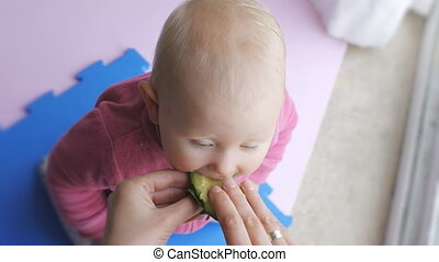 Baby eating avocado from mother's hands.
