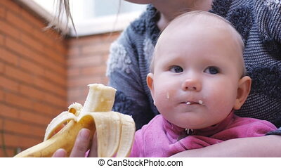 Baby eating banana from hands of mother