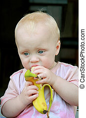 Baby Eating Banana - a cute little baby boy is eating a...