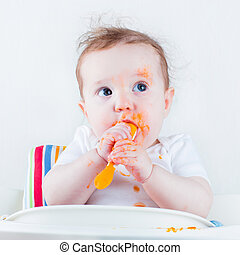 Baby eating carrot - Sweet messy baby eating a carrot in a...