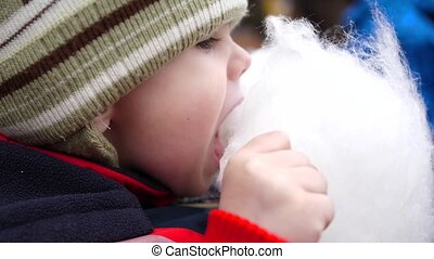 Baby eating cotton candy in the Park. Sweet and airy dessert...