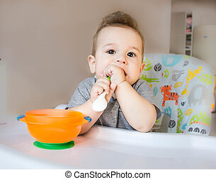 Baby eating food with a spoon, toddler eating messy and getting dirty infant having oatmeal as breakfast