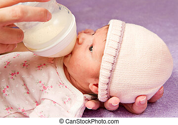 baby eating from a bottle