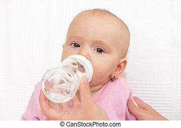 Baby eating from milk bottle