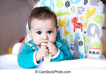 baby eating vegetables. in a high chair. teething , the cucumber, the concept of food, feeding . Newborn home. healthy . The first child eat nutritious snacks.