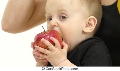 Baby eats an apple, next to her mother. White background. Slow motion. Close up