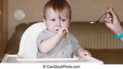 Baby eats yogurt at home