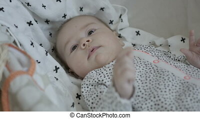 Cute baby falling asleep while lying on soft white blanket with cross pattern.