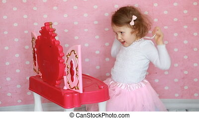 Baby fashionista plays a real lady. Child girl dresses up,...
