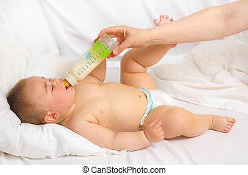 Baby feeding - Feeding procedure from milk bottle of a ...
