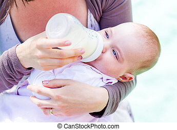 Young mother feeding her baby with milk bottle