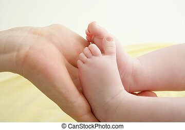 baby feet in mother hands playing