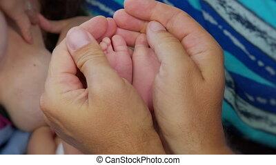 Baby feet in mother. Tiny Newborn Baby