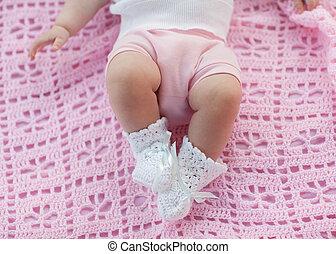 Baby feet in motion. Newborn lying on a pink blanket.