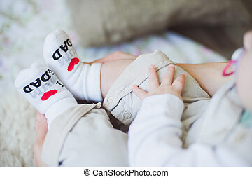 Baby feet in socks with funny inscription