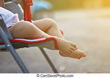 Baby feet in stroller outdoor.